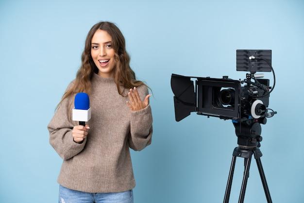 Reporter młoda kobieta trzyma mikrofon i donosi wiadomości z niespodzianką wyrazem twarzy