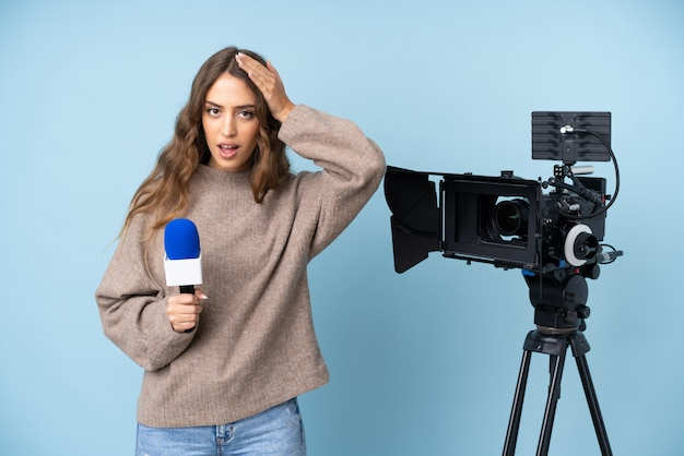 Reporter młoda kobieta trzyma mikrofon i donosi wiadomości z zaskoczonym wyrazem twarzy