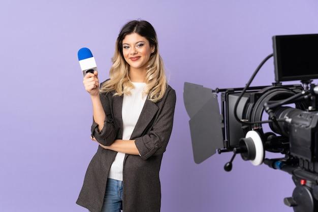 Reporter młoda kobieta trzyma mikrofon i raportuje wiadomości odizolowywających na purpurowej ścianie utrzymuje ręki krzyżować w frontowej pozyci