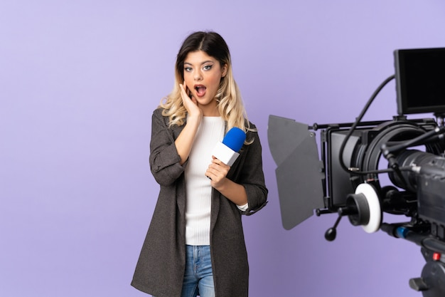 Reporter nastolatka trzyma mikrofon i donosi wiadomości na fioletowej ścianie zaskoczony i zszokowany, patrząc w prawo