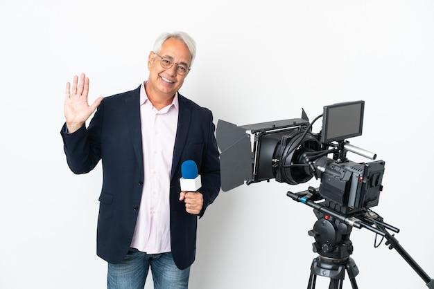 Reporter średniowieczny brazylijski mężczyzna trzymający mikrofon i relacjonujący wiadomości na białym tle salutujący ręką z radosnym wyrazem twarzy