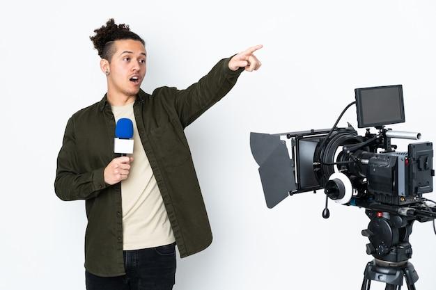 Reporter, trzymając mikrofon i wskazując na wiadomości, informuje