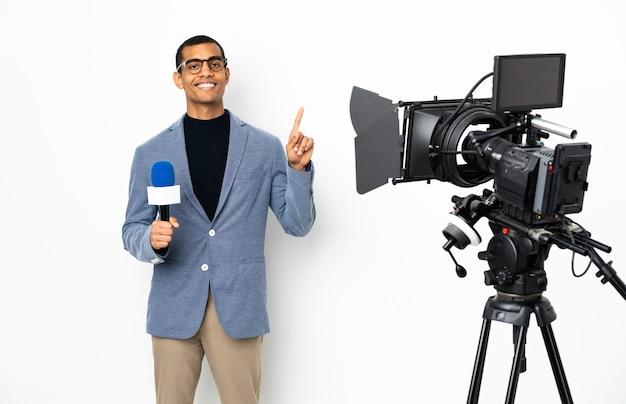 Reporter trzymający mikrofon i przekazujący wiadomości nad izolowaną białą ścianą pokazujący i podnoszący palec na znak najlepszych