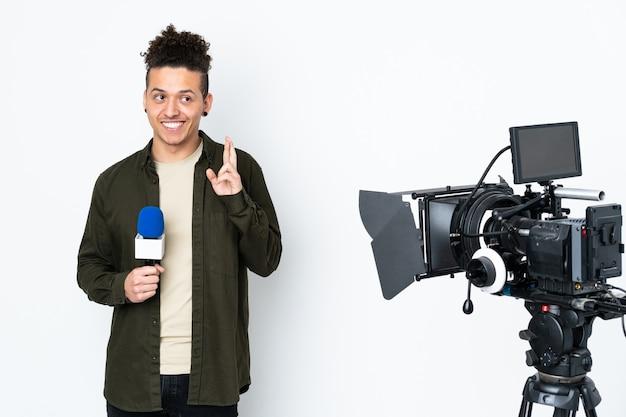 Reporter trzymający mikrofon i przekazujący wiadomości ze skrzyżowanymi palcami