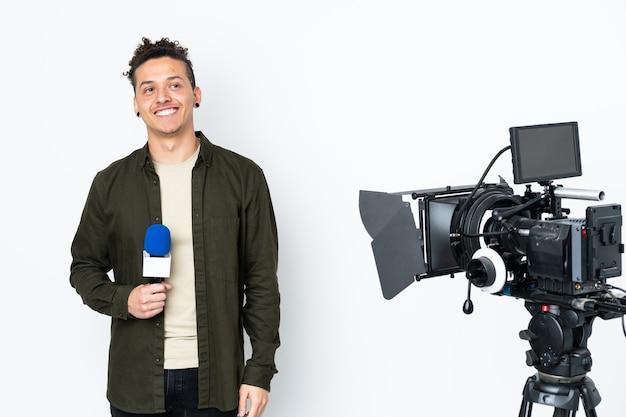 Reporter trzymający mikrofon i zgłaszający wiadomości, śmiejąc się i patrząc w górę