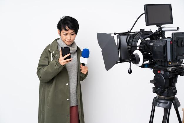Reporter wietnamska kobieta trzyma mikrofon i donosi wiadomości, myśląc i wysyłając wiadomość