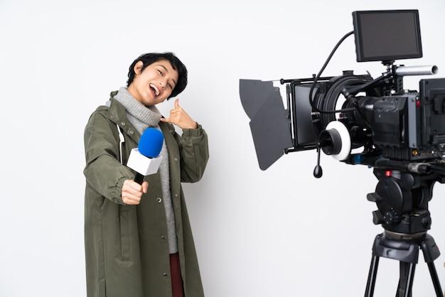 Reporter wietnamska kobieta trzyma mikrofon i donosi wiadomości, wykonując gest telefonu i wskazując przód