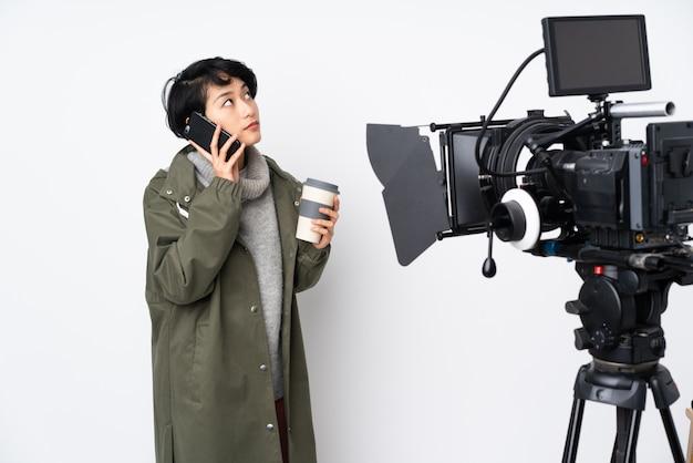 Reporter wietnamska kobieta trzyma mikrofon i donosi wiadomości z kawą na wynos i telefon komórkowy