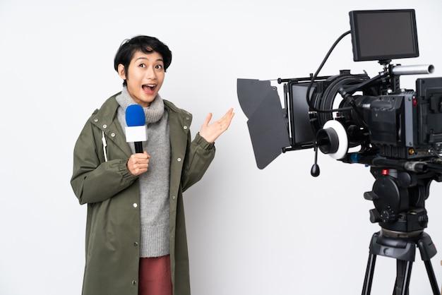 Reporter wietnamska kobieta trzyma mikrofon i donosi wiadomości ze zdziwionym wyrazem twarzy