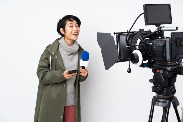 Reporter wietnamska kobieta z mikrofonem i informująca o nowościach zaskoczona i wysyłająca wiadomość