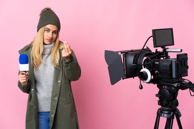 Reporterka kobieta trzyma mikrofon i zgłasza wiadomości nad izolowaną różową ścianą, czyniąc gest pieniędzy