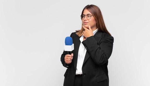 Reporterka młoda kobieta uśmiecha się z radosną, pewną siebie miną, z ręką na brodzie, zastanawia się i patrzy w bok