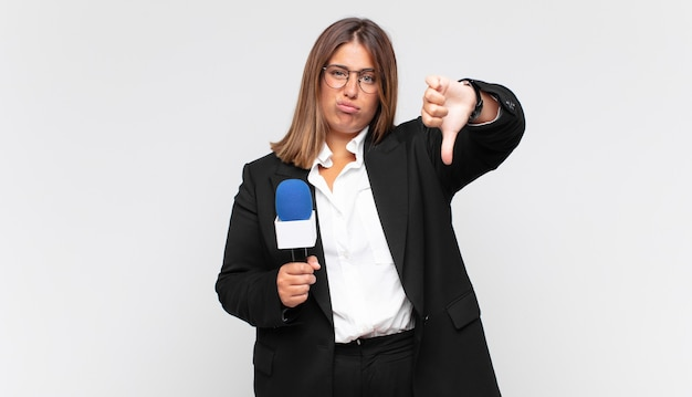 Reporterka młodej kobiety czuje się zła, zła, zirytowana, rozczarowana lub niezadowolona, pokazuje kciuki w dół z poważnym spojrzeniem