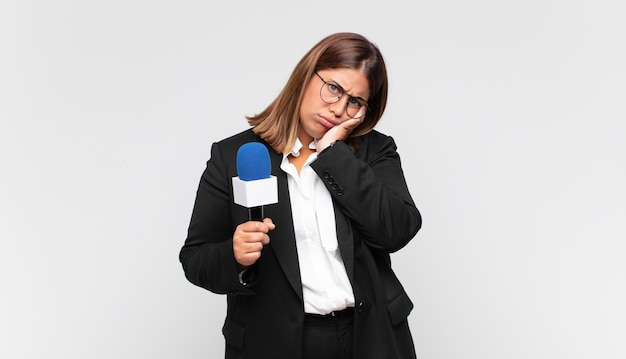 Reporterka młodej kobiety czuje się znudzona, sfrustrowana i senna po męczącym, nudnym i żmudnym zadaniu, trzymając twarz ręką