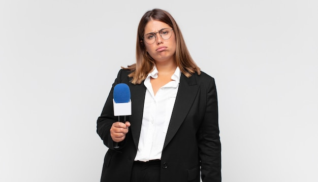 Reporterka młodej kobiety smutna i jęcząca z nieszczęśliwym spojrzeniem, płacząca z negatywnym i sfrustrowanym nastawieniem