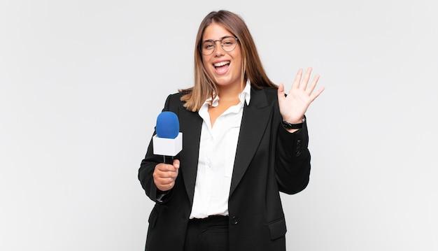 Reporterka młodej kobiety uśmiechnięta radośnie i wesoło, machająca ręką, witająca i witająca lub żegnająca się