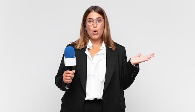 Reporterka młodej kobiety wyglądająca na zaskoczoną i zszokowaną, z opadniętą szczęką trzymającą przedmiot z otwartą ręką z boku