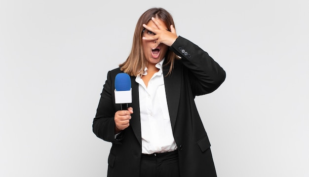 Reporterka młodej kobiety wyglądająca na zszokowaną, przestraszoną lub przerażoną, zakrywającą twarz dłonią i zaglądającą między palce