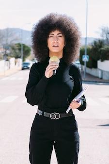 Reporterka telewizyjna, dziennikarka z afro włosami, relacjonująca wiadomość z ulicy