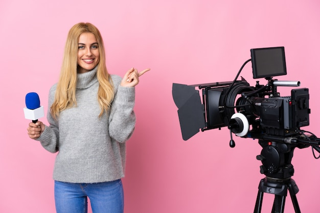 Reporterka trzyma mikrofon i donosi o nowościach na różowym tle, wskazując na bok, aby przedstawić produkt