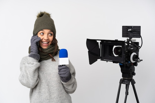 Reporterka trzyma mikrofon i przekazuje wiadomości na białym tle trzymając kawę na wynos i telefon komórkowy