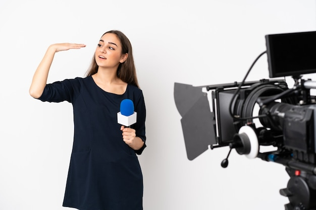 Reporterka trzymając mikrofon i zgłaszając wiadomości na białej ścianie z wyrazem zmęczenia i choroby
