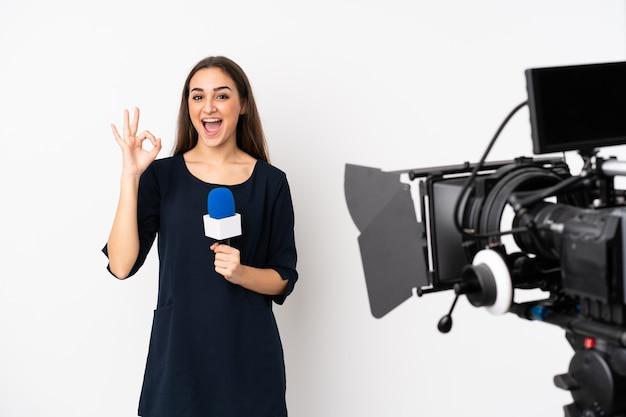 Reporterka trzymając mikrofon i zgłaszając wiadomości na białym tle na białej ścianie, pokazując znak ok i kciuk w górę gest