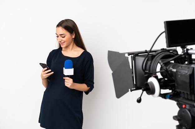 Reporterka trzymająca mikrofon i informująca o nowościach na białej ścianie wysyłająca wiadomość z telefonu komórkowego