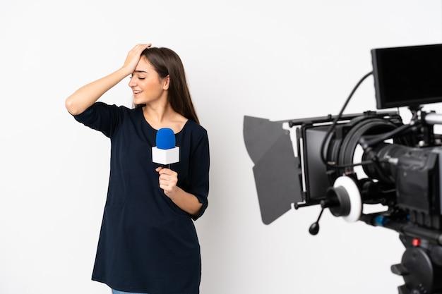 Reporterka trzymająca mikrofon i przekazująca wiadomości na białej ścianie coś sobie uświadomiła i zamierza znaleźć rozwiązanie