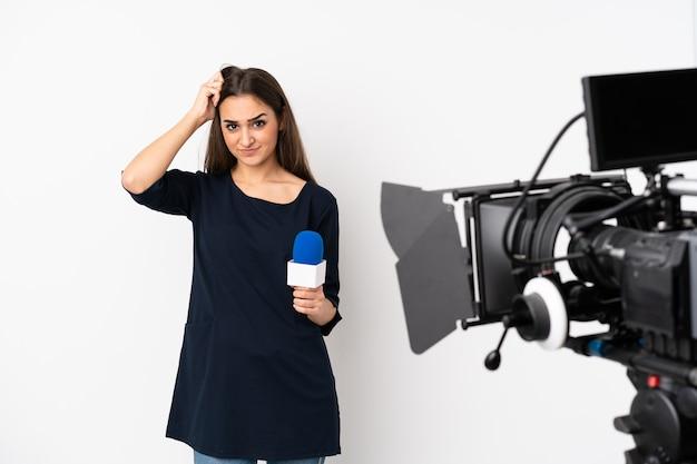 Reporterka trzymająca mikrofon i przekazująca wiadomości na białej ścianie z wyrazem frustracji i niezrozumienia