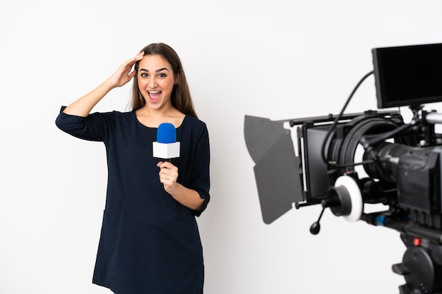Reporterka trzymająca mikrofon i przekazująca wiadomości na białej ścianie zaskoczona i wskazując palcem w bok
