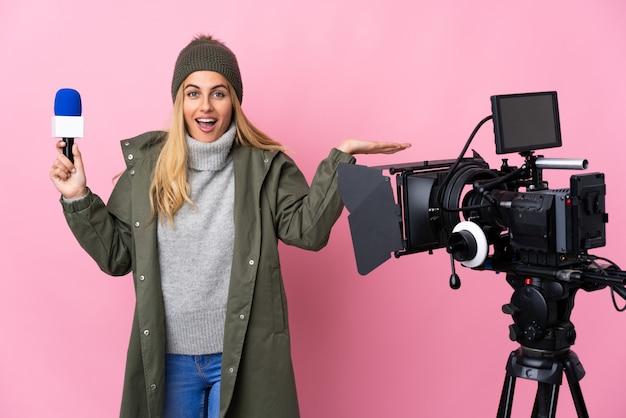 Reporterka trzymająca mikrofon i przekazująca wiadomości na białym tle różowym z zszokowanym wyrazem twarzy