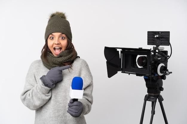Reporterka trzymająca mikrofon i przekazująca wiadomości na białym tle zaskoczona i wskazująca strona