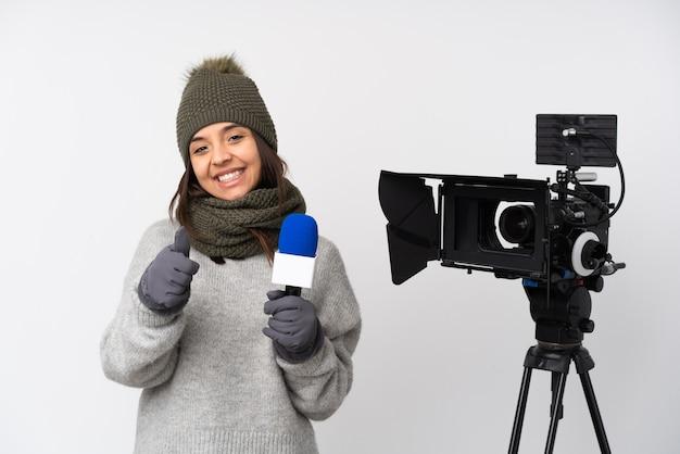 Reporterka trzymająca mikrofon i przekazująca wiadomości na odosobnionym białym tle z kciukami do góry, ponieważ wydarzyło się coś dobrego