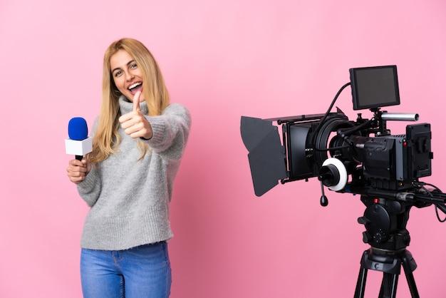 Reporterka trzymająca mikrofon i przekazująca wiadomości nad izolowaną różową ścianą z kciukami do góry, ponieważ wydarzyło się coś dobrego