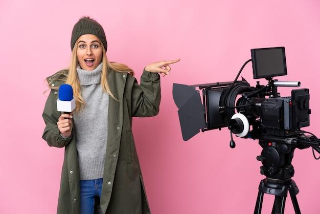 Reporterka trzymająca mikrofon i przekazująca wiadomości nad izolowaną różową ścianą zaskoczona i wskazując palcem w bok