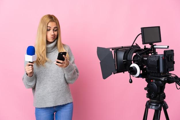 Reporterka trzymająca mikrofon i przekazująca wiadomości nad odosobnionym różowym myśleniem i wysyłaniem wiadomości