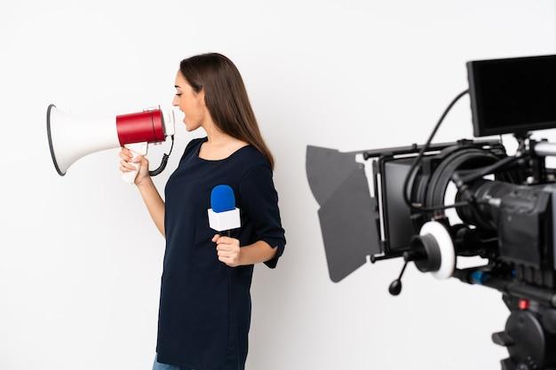 Reporterka trzymająca mikrofon i zgłaszająca wiadomości na białej ścianie krzycząca przez megafon