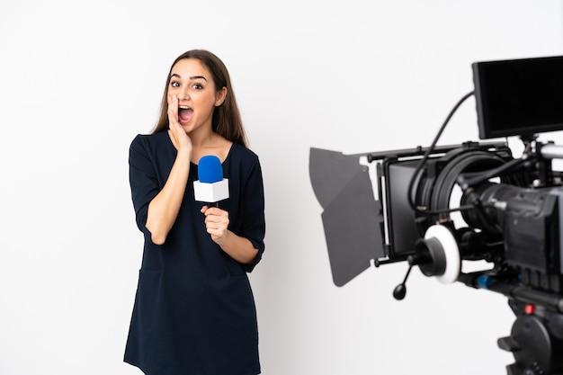 Reporterka trzymająca mikrofon i zgłaszająca wiadomości na białej ścianie z zaskoczeniem i zszokowanym wyrazem twarzy