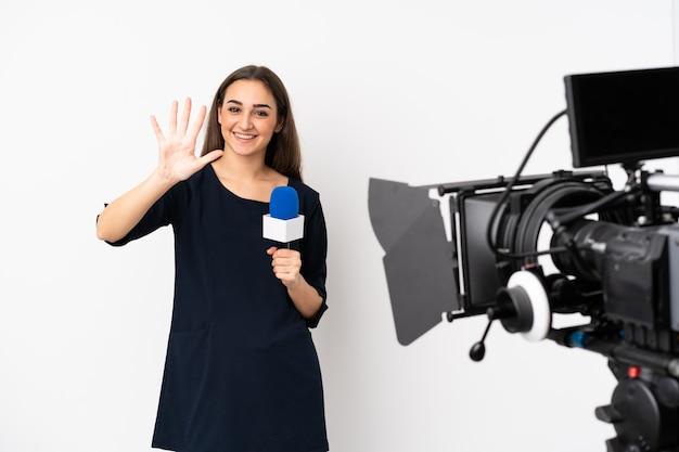 Reporterka trzymająca mikrofon i zgłaszająca wiadomości na białym tle na białej ścianie, licząc pięć palcami