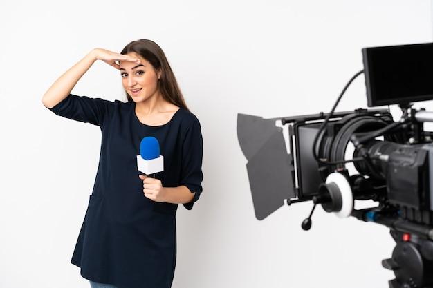 Reporterka trzymająca mikrofon i zgłaszająca wiadomości na białym tle na białej ścianie, patrząc daleko ręką, aby coś spojrzeć