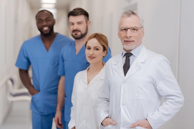 Reprezentowanie mojej międzynarodowej kadry. sympatyczny, brodaty, doświadczony lekarz, cieszący się pracą w klinice i uśmiechając się prezentując personel