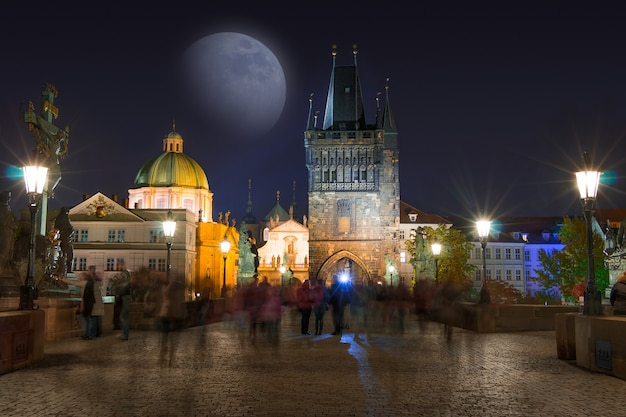 Republika czeska. praga. noc na moście karola i księżycu. wiele nierozpoznawalnych osób