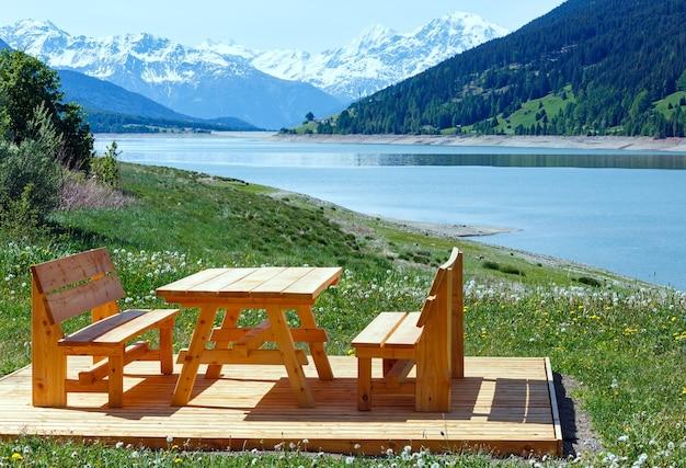 Reschensee (lub jezioro reschen) letni krajobraz z kwitnącą łąką piknikowa drewniana ławka w pobliżu (włochy)