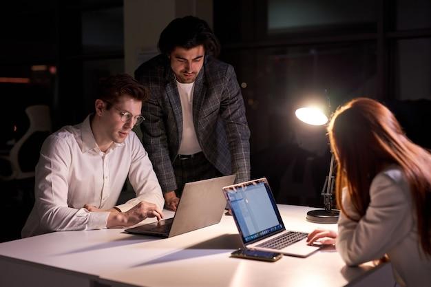 Responsive directore lub manager firmy pomagają współpracownikom dotrzymać terminu, nie mając czasu na sen i odpoczynek, widok z boku na ludzi biznesu pracujących wspólnie nad projektem startowym, przy użyciu laptopa