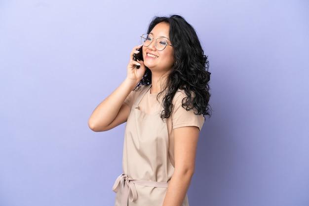 Restauracja azjatycki kelner na białym tle na fioletowym tle prowadząca rozmowę z telefonem komórkowym