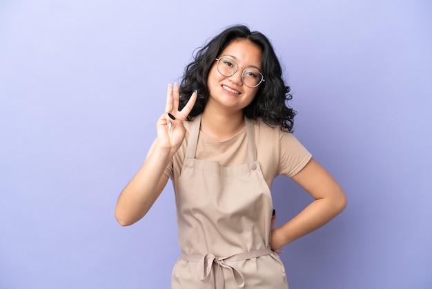 Restauracja azjatycki kelner na białym tle na fioletowym tle szczęśliwy i liczący trzy palcami