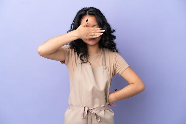 Restauracja azjatycki kelner na białym tle na fioletowym tle zasłaniając oczy rękami. nie chcę czegoś widzieć