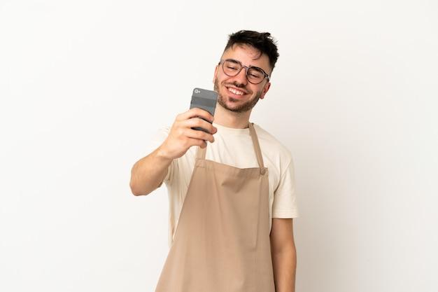 Restauracja kelner kaukaski mężczyzna na białym tle robi selfie