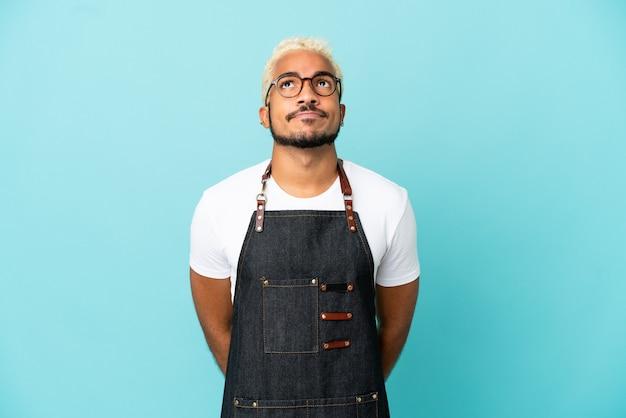 Restauracja kolumbijski kelner mężczyzna na białym tle na niebieskim tle i patrząc w górę